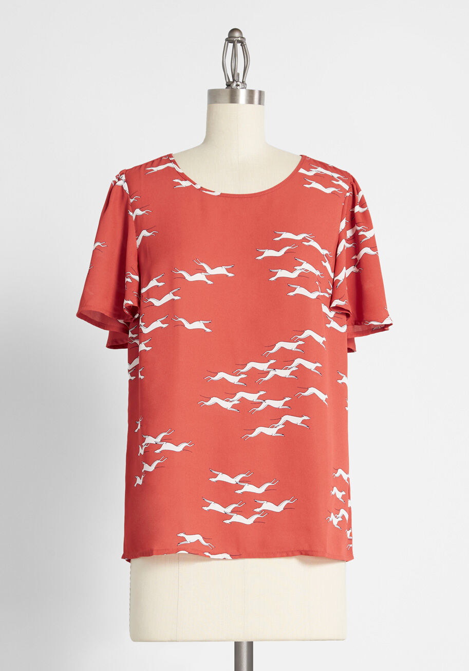 A scoop-neck top with ruffle sleeves in red with illustrations of white greyhounds running all over it