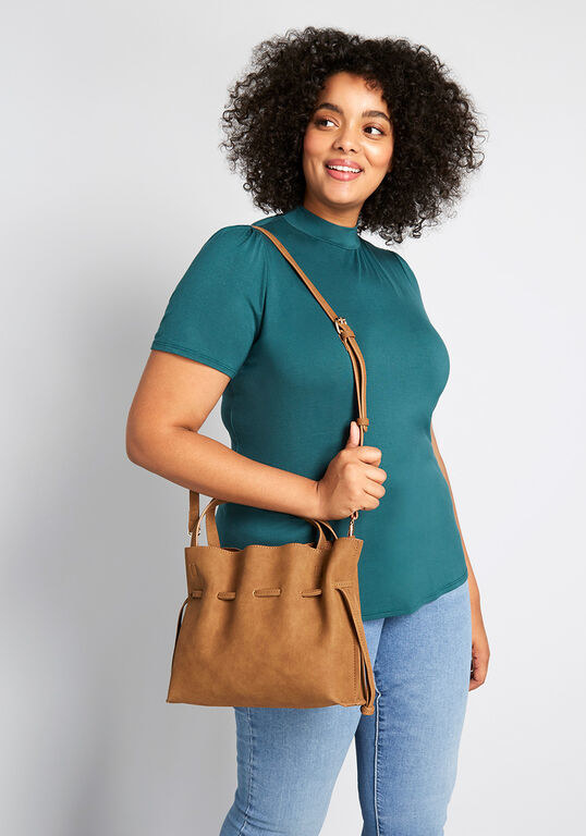 Model holding the tote bag with draw-string close and short straps over their shoulder