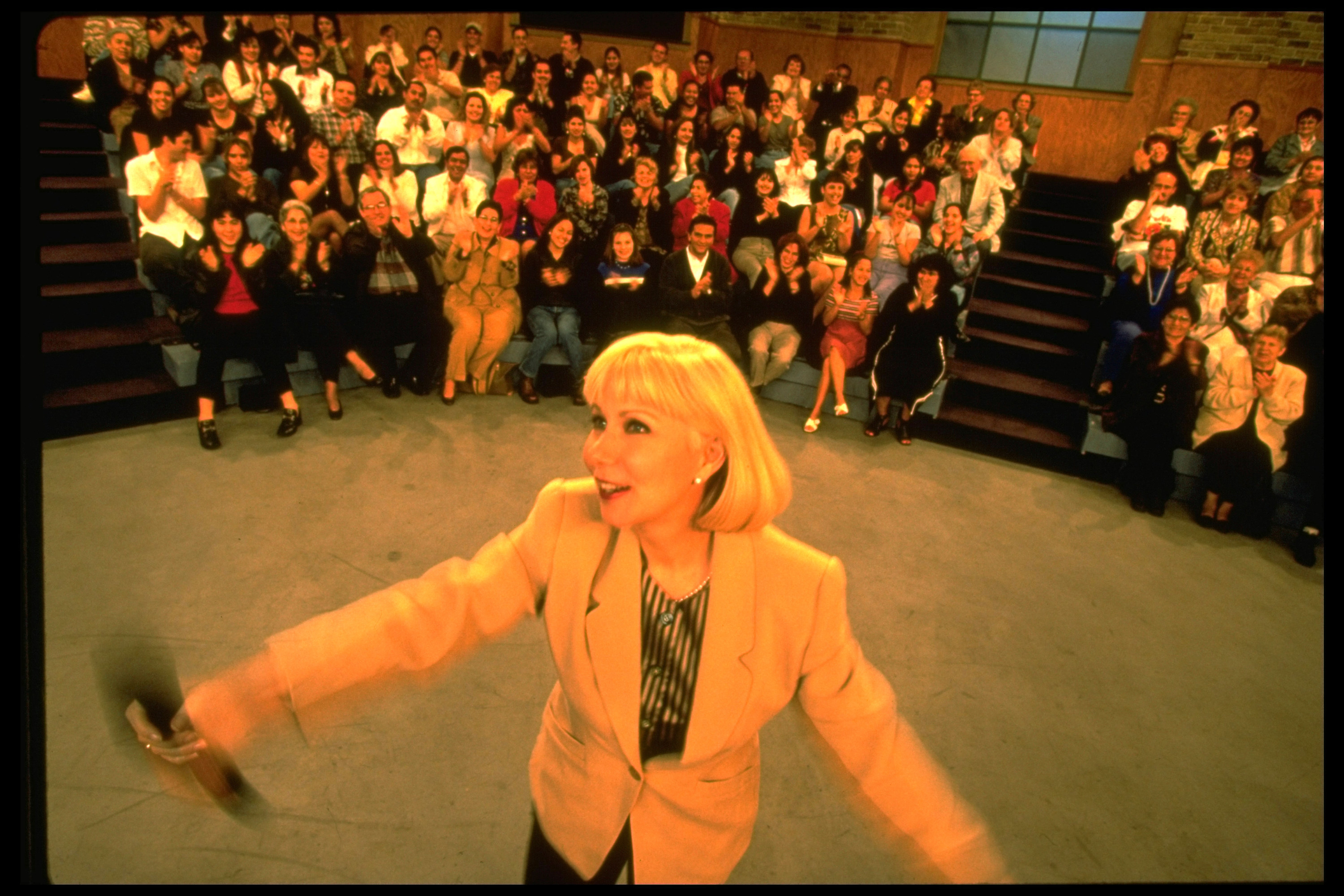 A photo Cristina Saralegui dancing with the audience behind her applauding on the set of her show