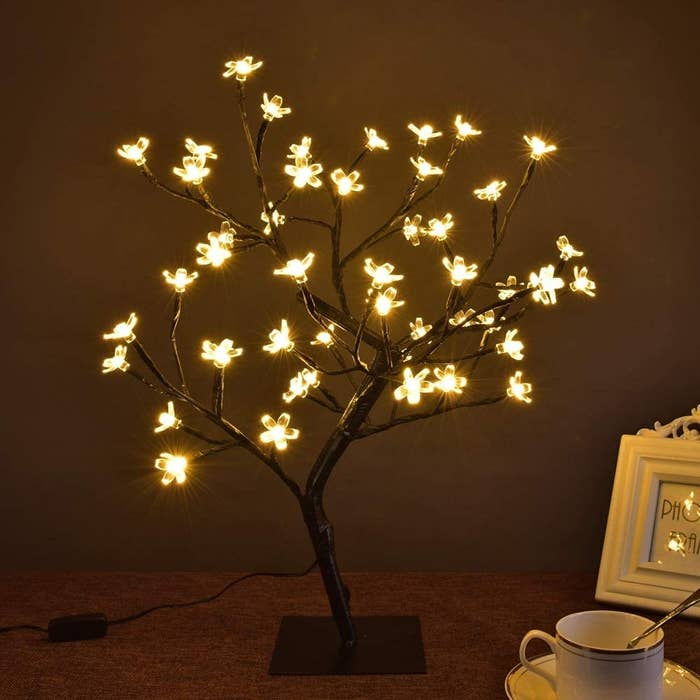 A tree with LED cherry blossoms is lit on a table