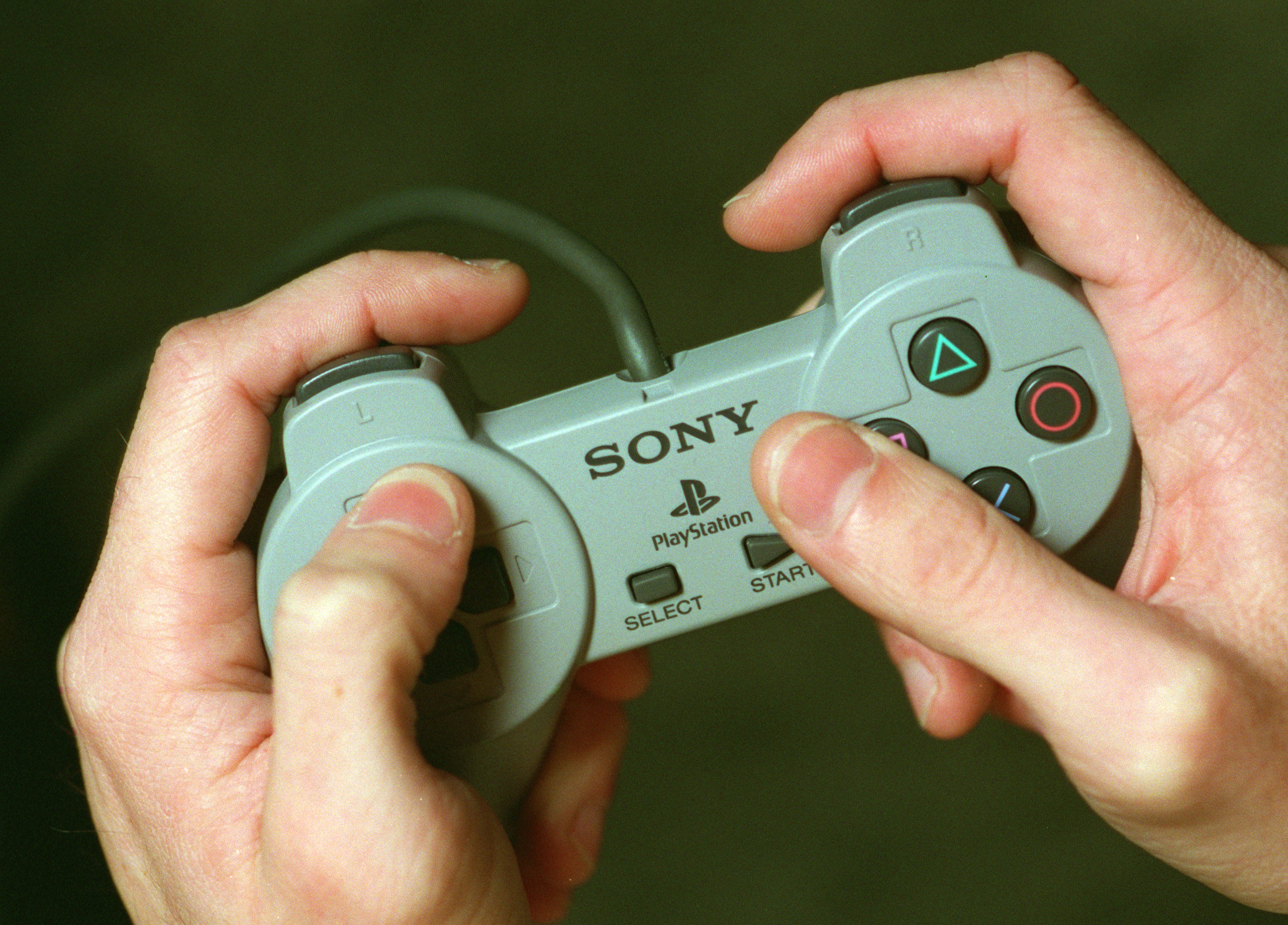 A set of hands holding a Sony PlayStation remote