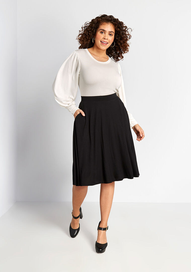 Model wearing the a-line skirt with an elastic waist, and hand in the pocket on the side