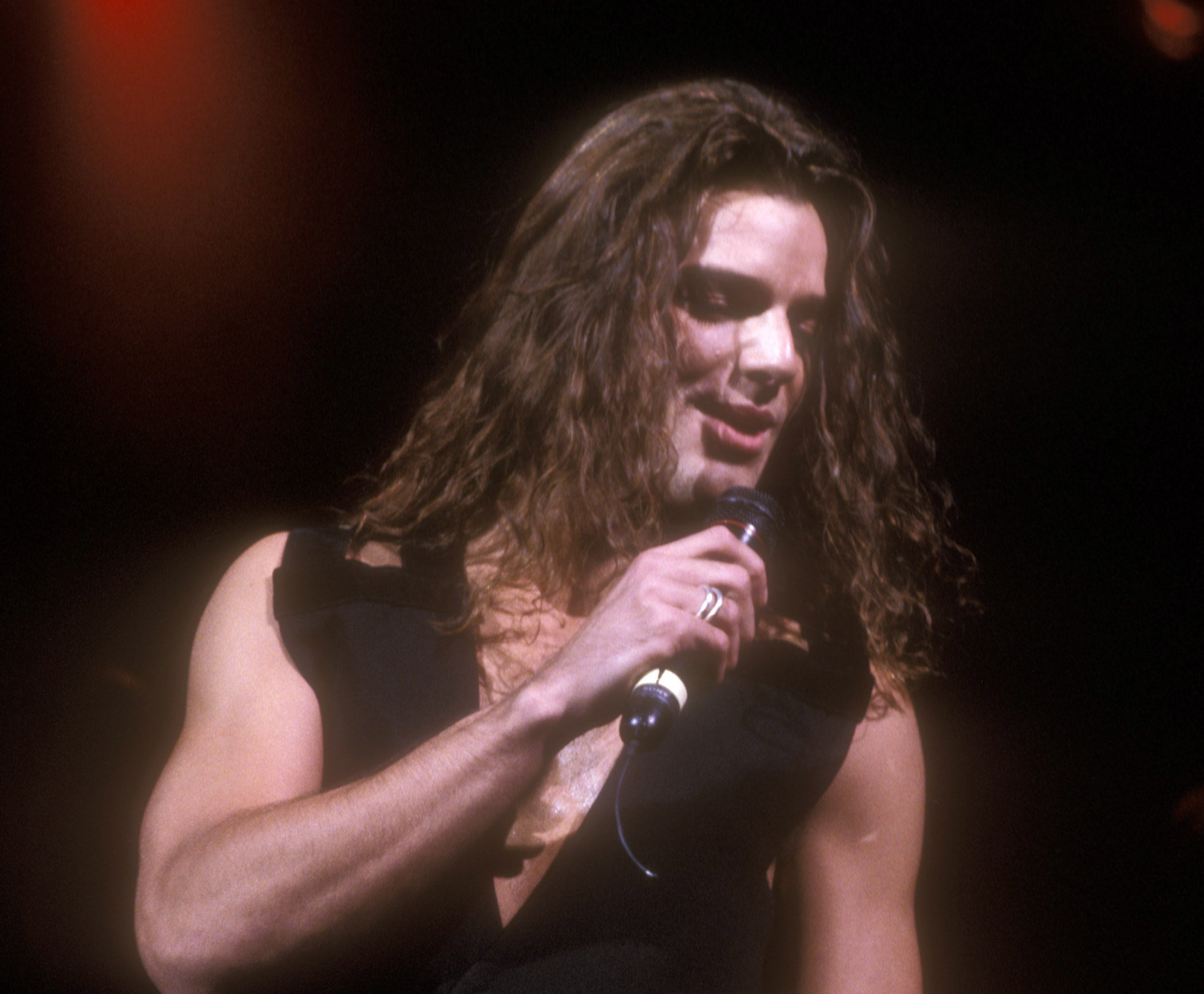 Ricky Martin performing a concert with shoulder-length hair and wearing only a vest