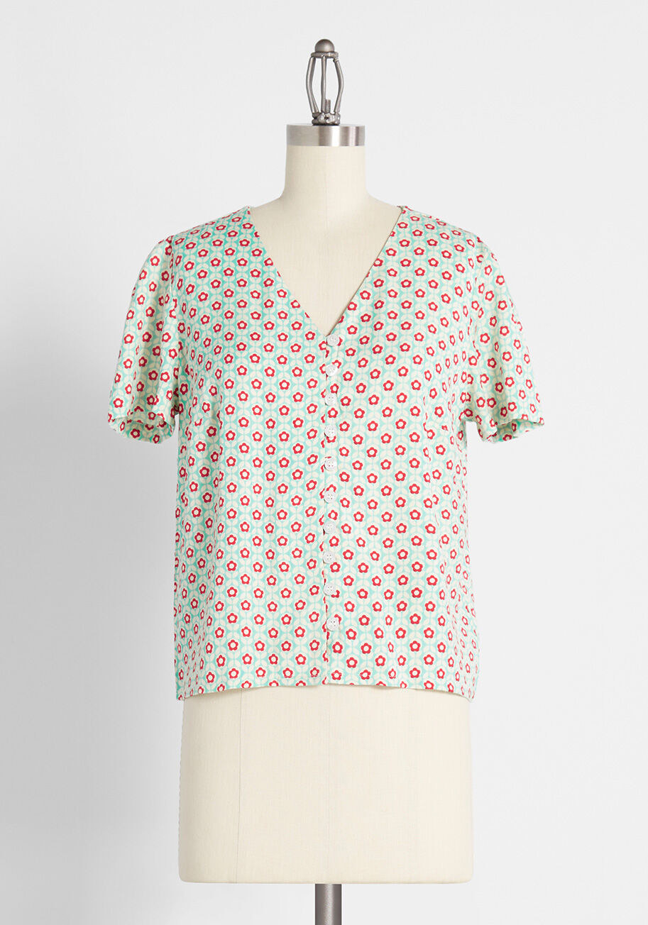 The top in light green with white and red daisies all around it and buttons down the middle