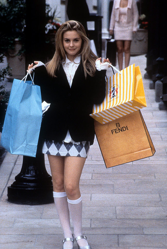 A publicity photo of Alicia Silverstone as Cher in Clueless holding bags on Rodeo Drive