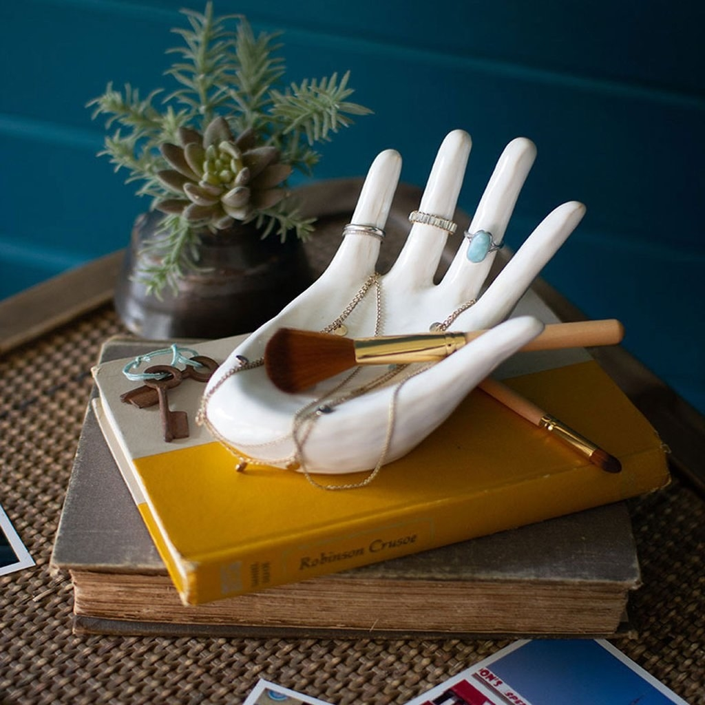 white ceramic dish shaped like a hand holding rings, necklaces, and a makeup brush