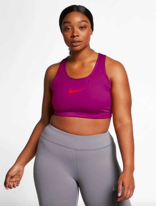 Model wears dark pink Nike Medium Support Sports Bra with gray leggings