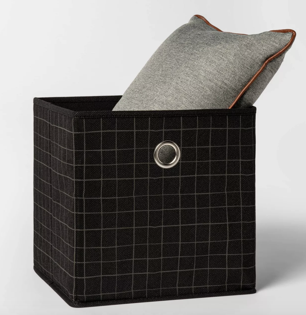 black fabric cube with thin grey grid print holding pillow