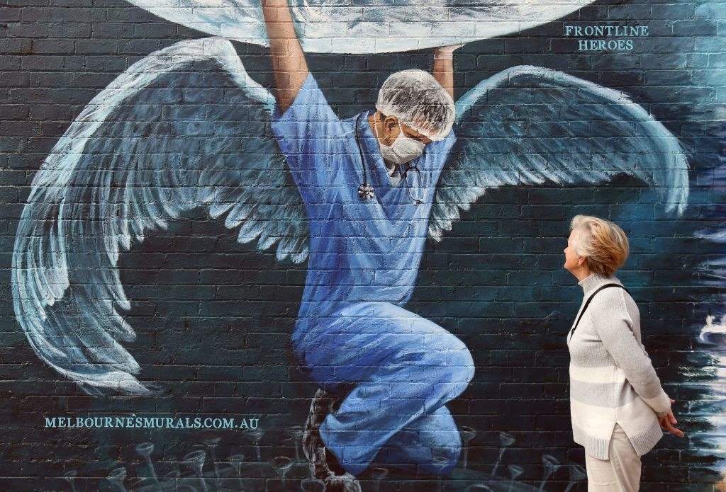 A mural depicts a nurse with angel wings holding up the world