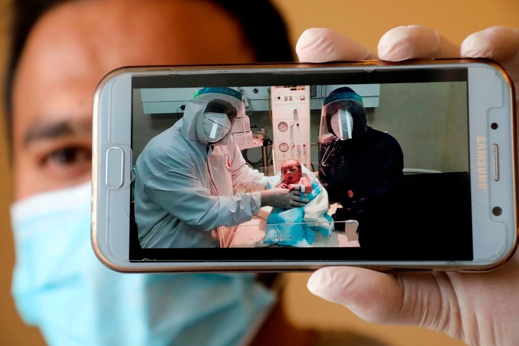 A man holds holds up a phone FaceTiming the birth of a baby