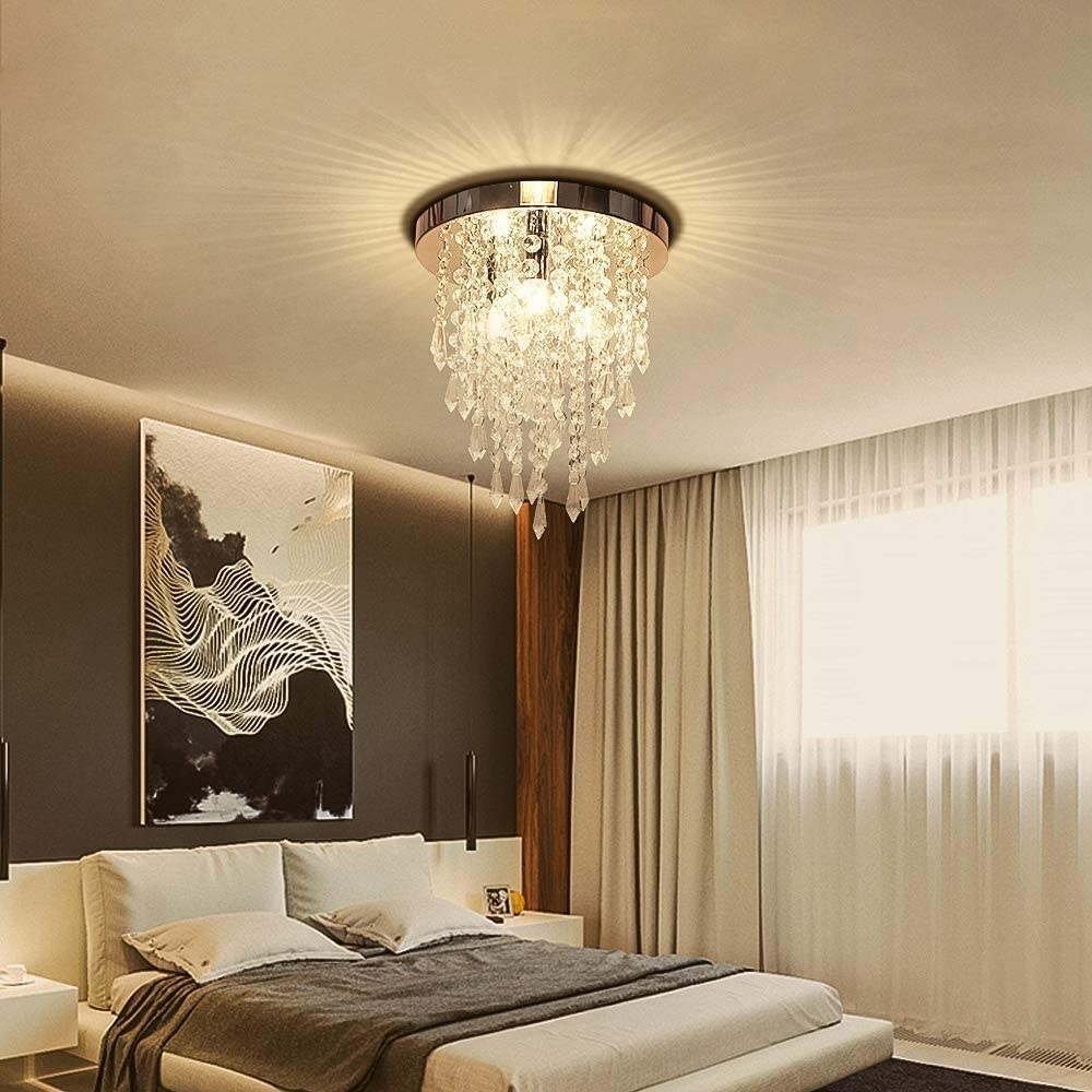 A chandelier with strings of crystals hang in a bedroom