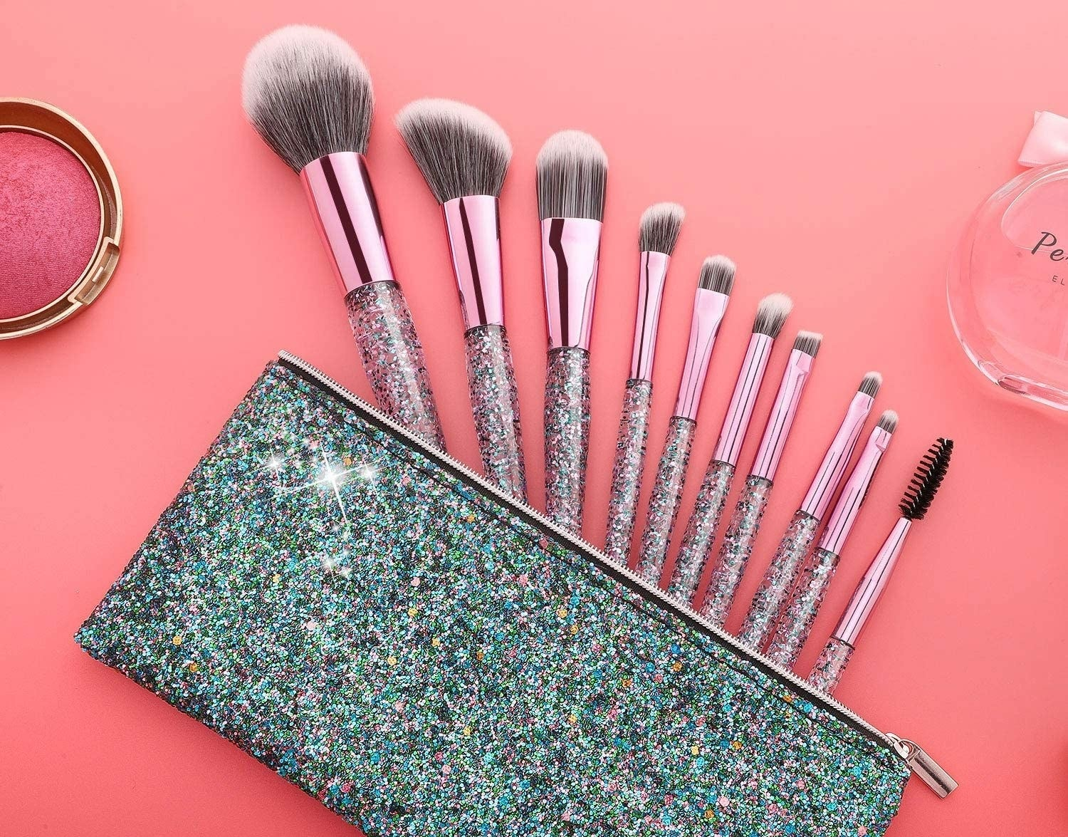 Nine makeup brushes with sparkly handles in a sparkly makeup bag