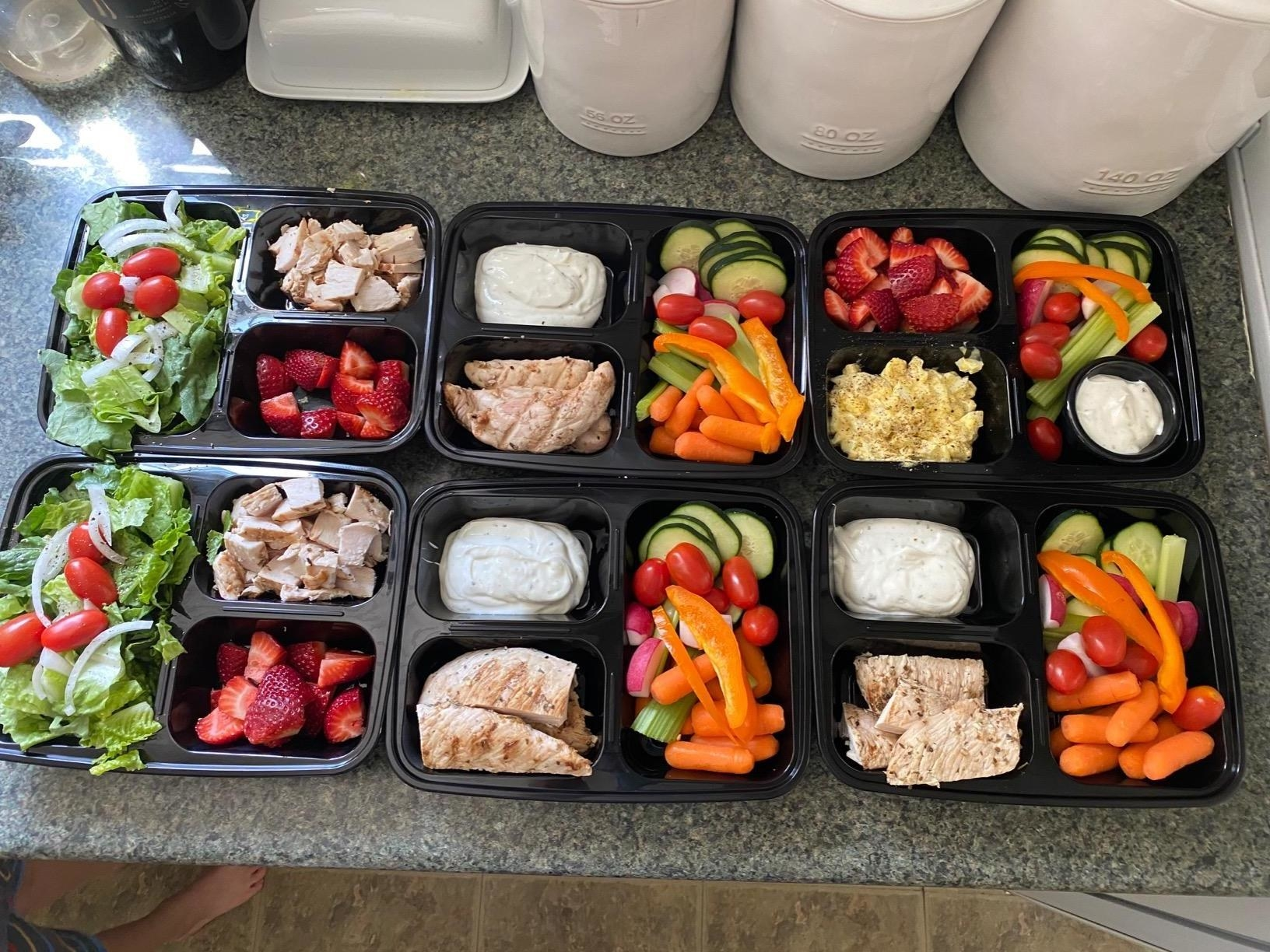 A reviewer showing the three-compartment containers holding meals they've prepared ahead