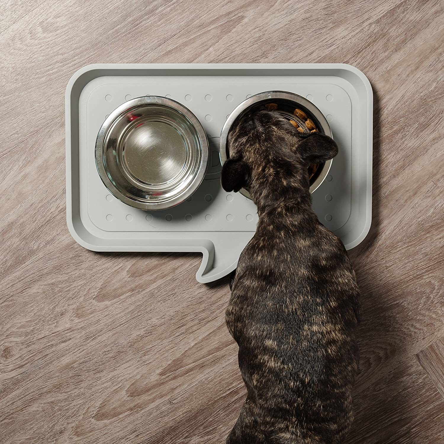 A French bulldog eating out of a bowl on the speech bubble mat