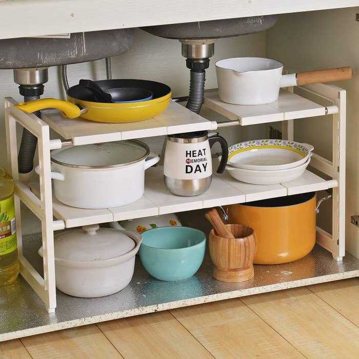 A white, plastic two-tier under-sink organizer