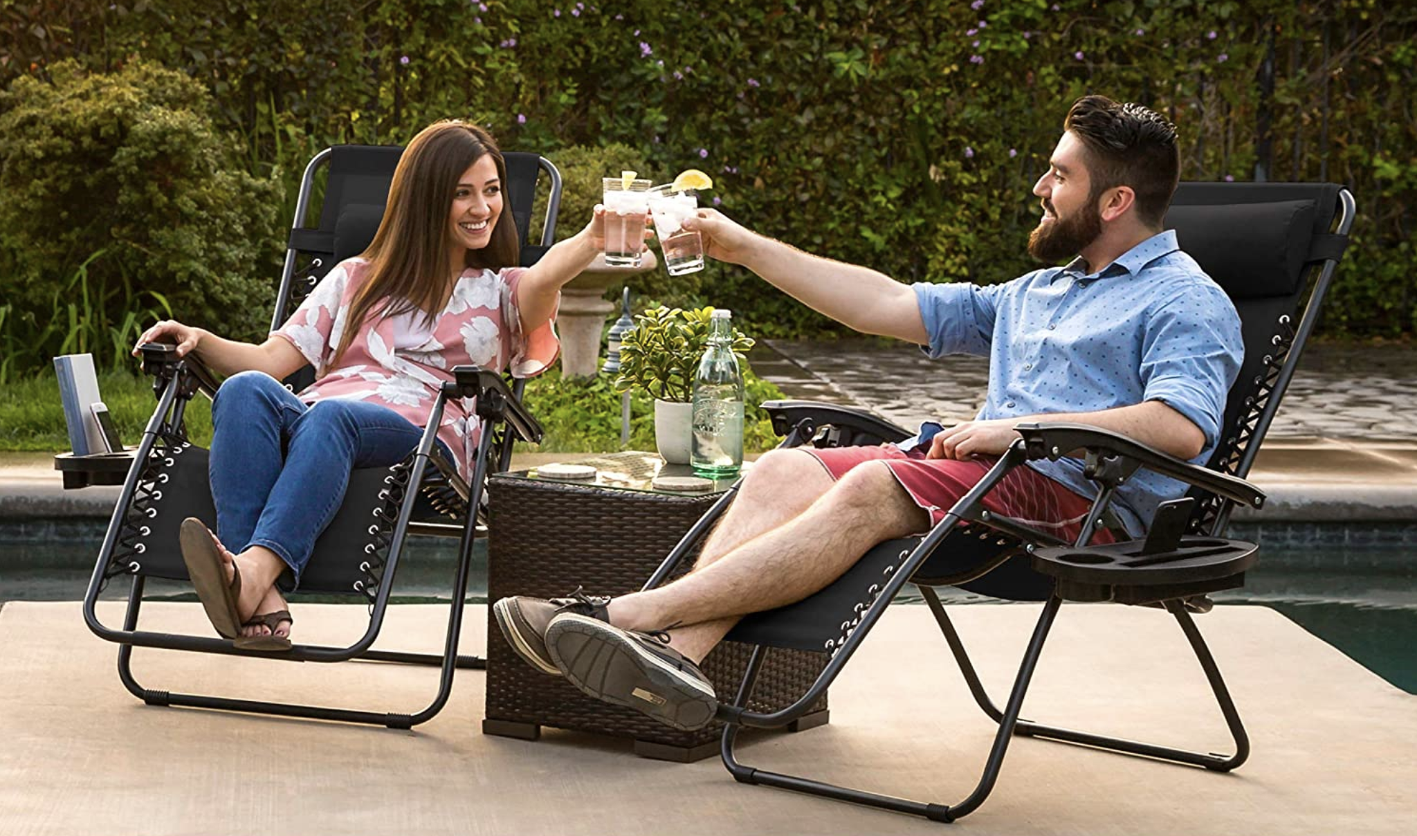 Two models in black recliners with objects in their drink holders