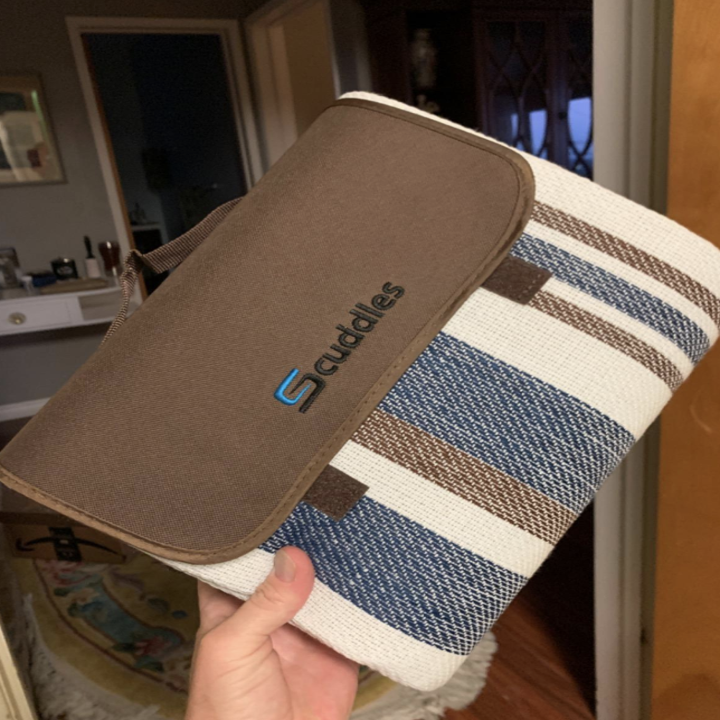 Reviewer holding up blanket rolled up with a carrying handle