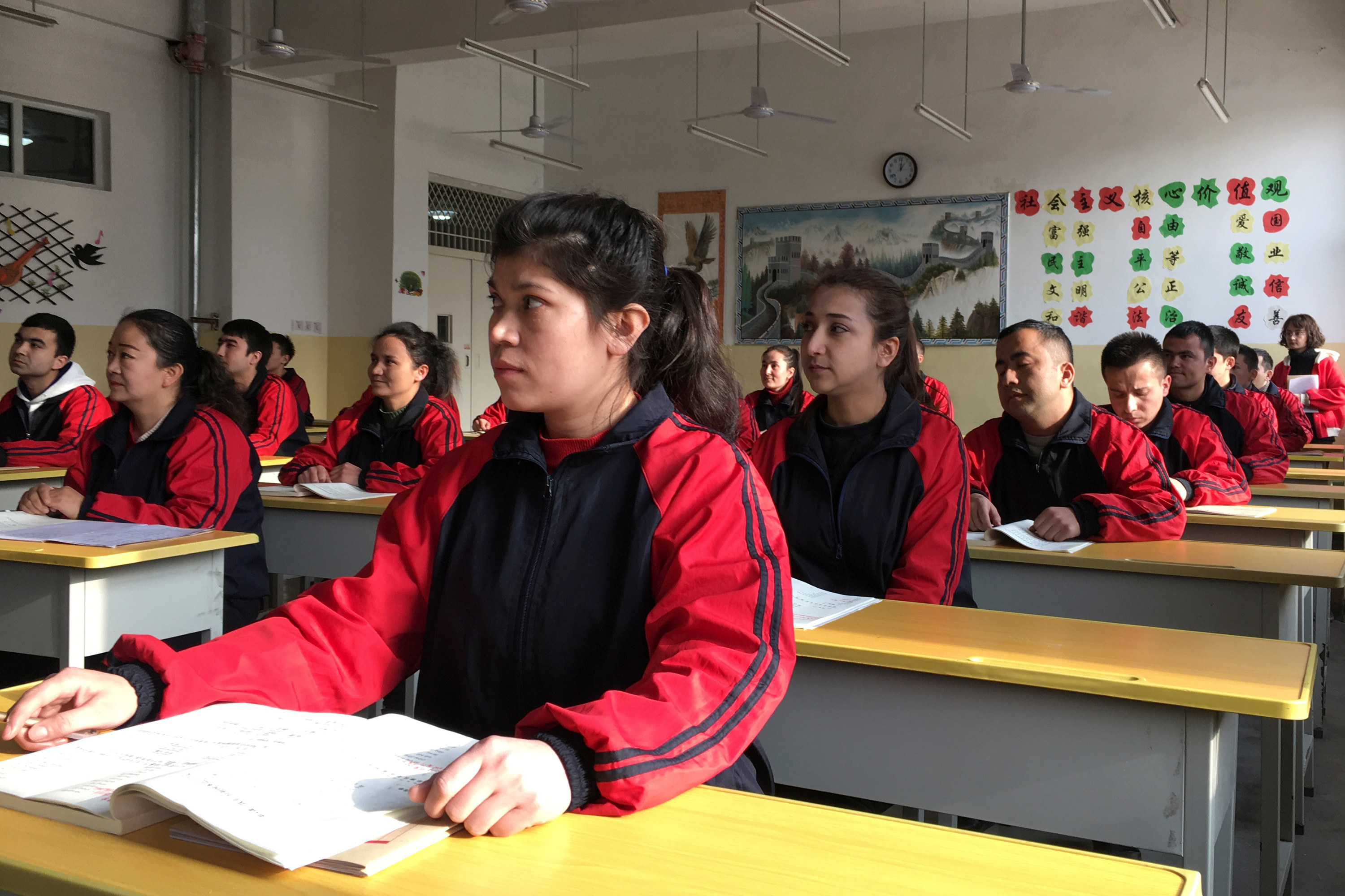 Adult students in matching jumpsuits sit in rows of desks