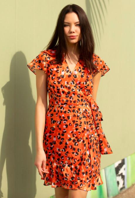 Model wears orange and black leopard-print wrap short-sleeve dress with ruffles