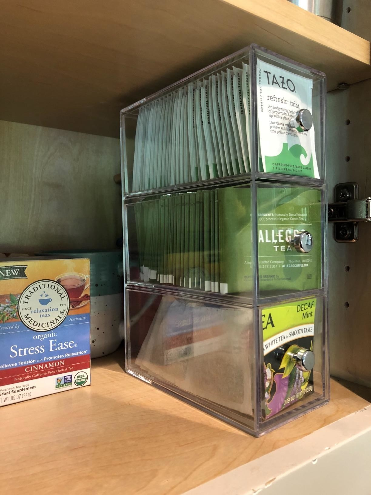 A clear plastic three drawer organizer filled with tea packets