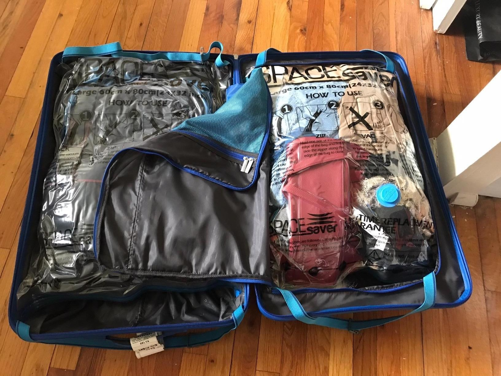 A reviewer's suitcase with clothes packed in two vacuum bags