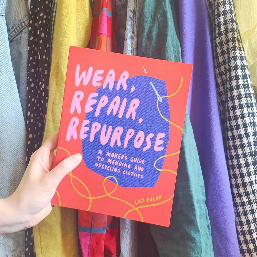 A person holding a book called Wear, Repair, Repurpose in front of a rack of clothing