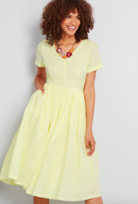Model wears light yellow fit-and-flare shirt dress with a colorful floral necklace