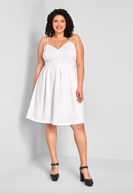Model wears white flair A-line dress with black pumps