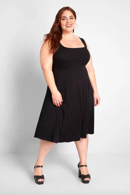 Model wears casual black midi sleeveless dress with matching heeled wedges