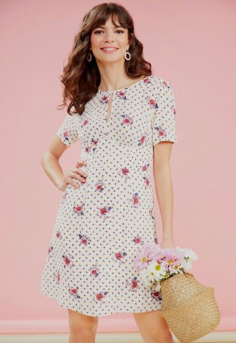 Model wears floral-print short sleeve keyhole dress while carrying a basket bag
