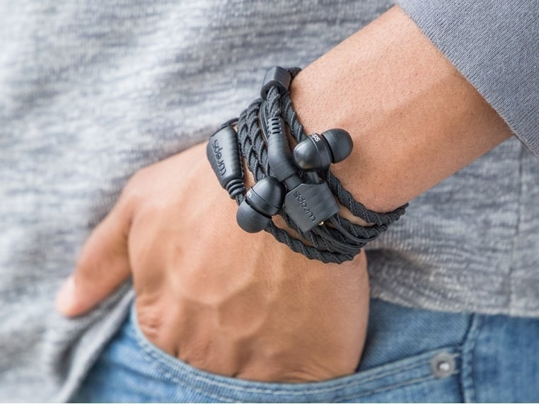 a model's wrist with a headphones wrapped around their wrist in a braided rope