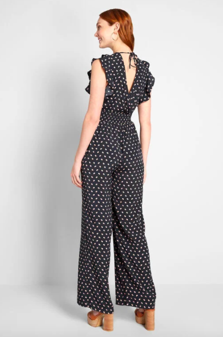 Model wears black polka-dot wide-leg sleeveless jumpsuit with high brown wedges