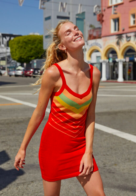Model wears red sleeveless tank dress with a colorful striped design on the front