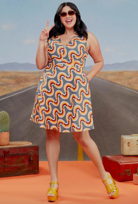 Model wears rainbow-print orange, red, blue, and yellow sleeveless dress with yellow platform sandals