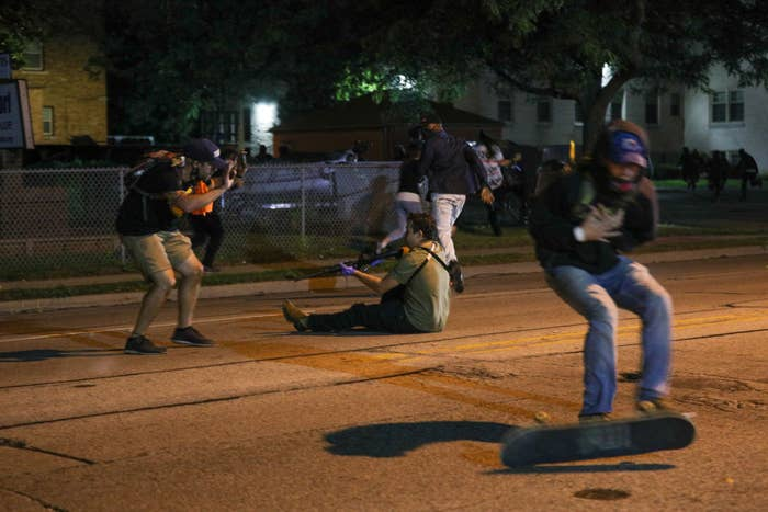 Someone sits on the street holding a long gun as protesters react and scatter, one in the foreground falls from a skateboard