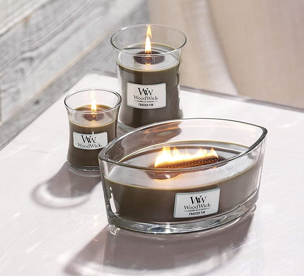 """three green candles in different sizes labeled """"WoodWick Frasier Fur"""""""