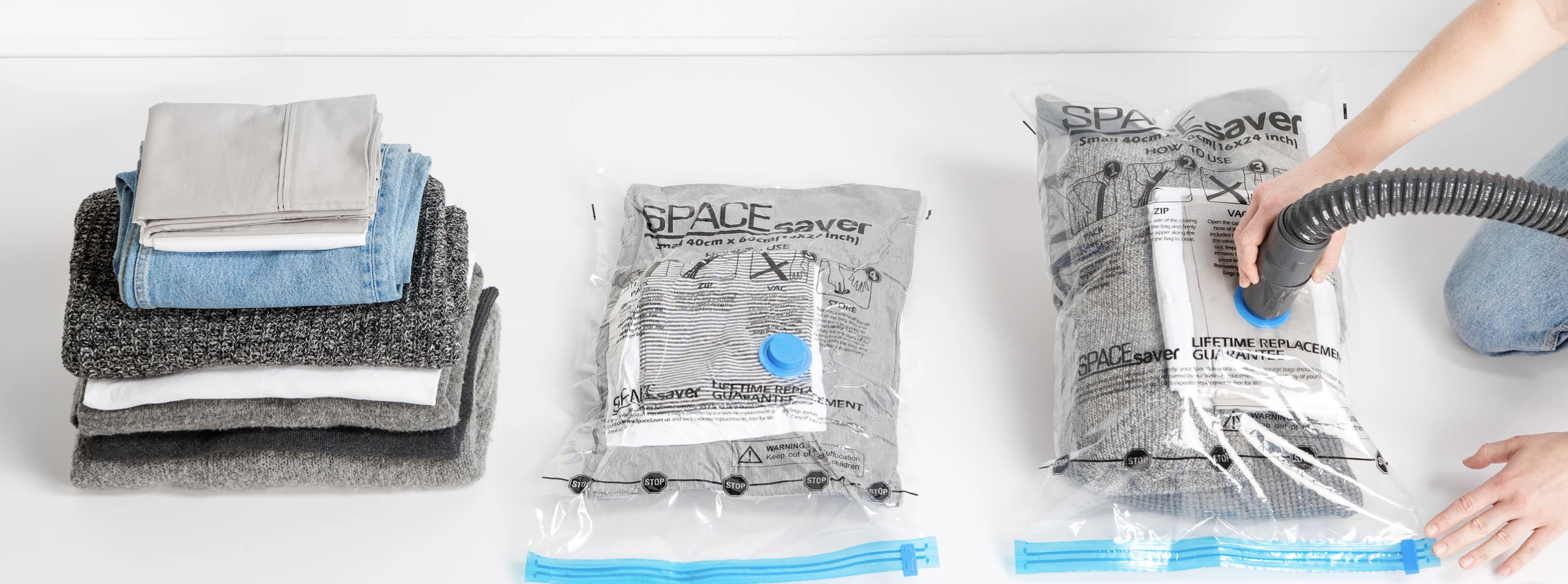 A stack of linens next to two of the bags, including one with a vacuum hose attached
