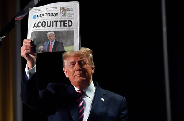 Trump holding a newspaper with the headline Acquitted