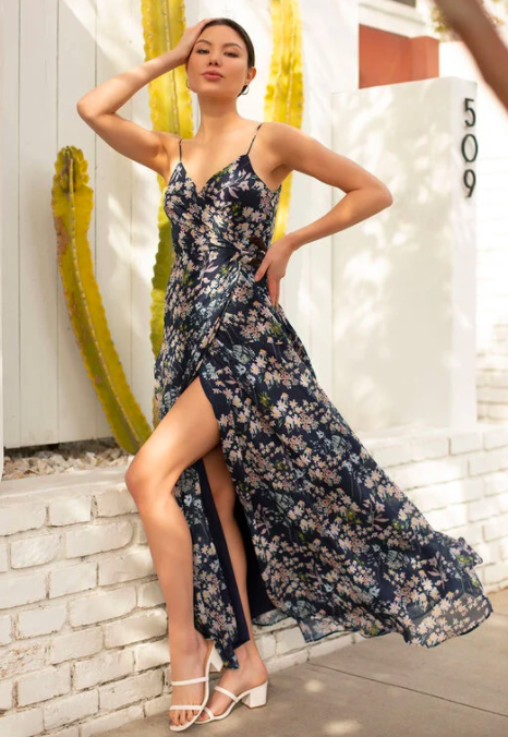 Model wears dark blue floral sleeveless maxi dress with a side-slit near the leg and white block-heel sandals