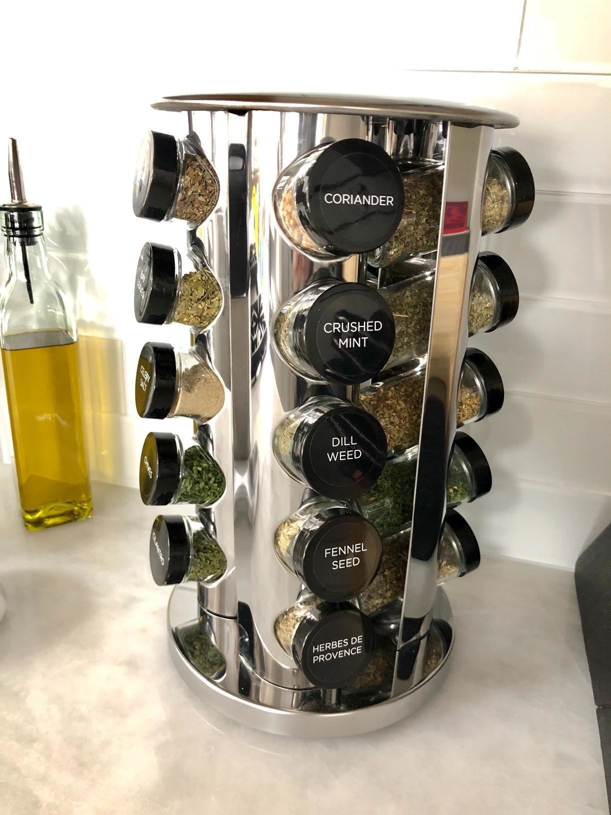 Mirrored spinning rack filled with spice jars with labeled black lids