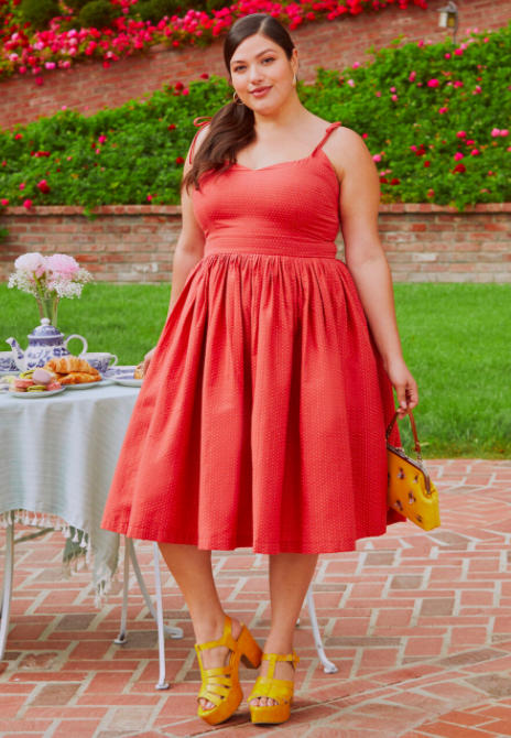 Model wears red tie-shoulder sleeveless dress with yellow platform sandals and a jeweled yellow purse