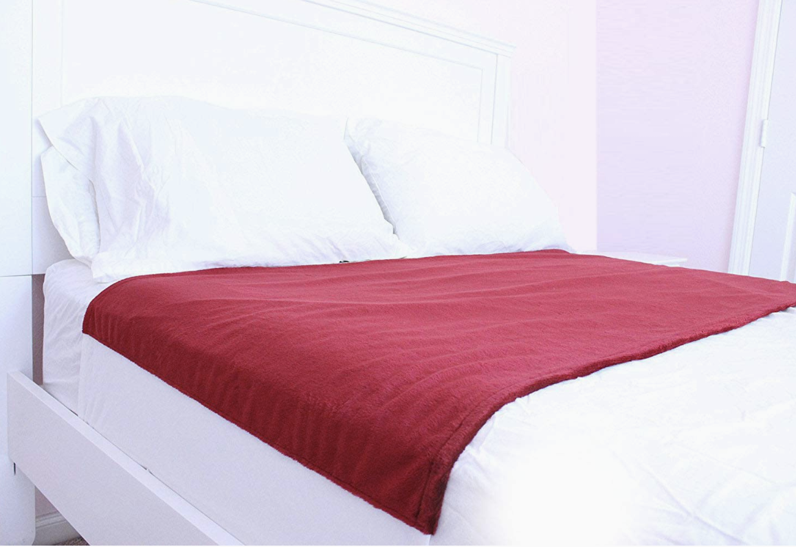 red sheet protector on top of bed sheets