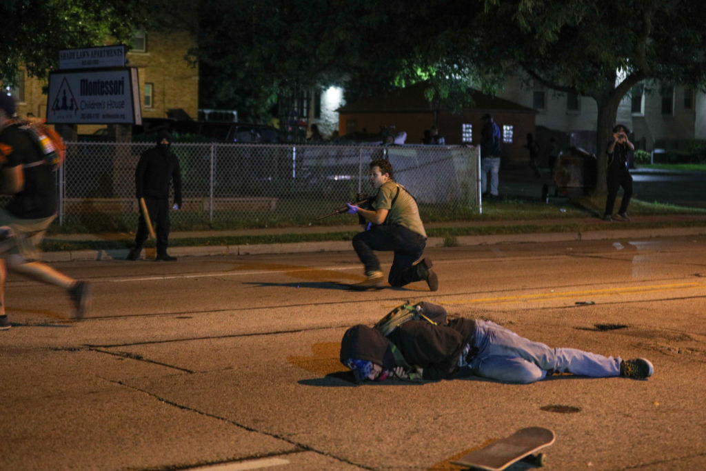A person lies on the ground near their skateboard, behind them, a man kneels with a long gun pointed in a different direction