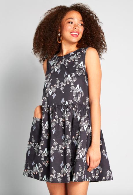 Model wears sleeveless black cactus print dress with an A-line shape