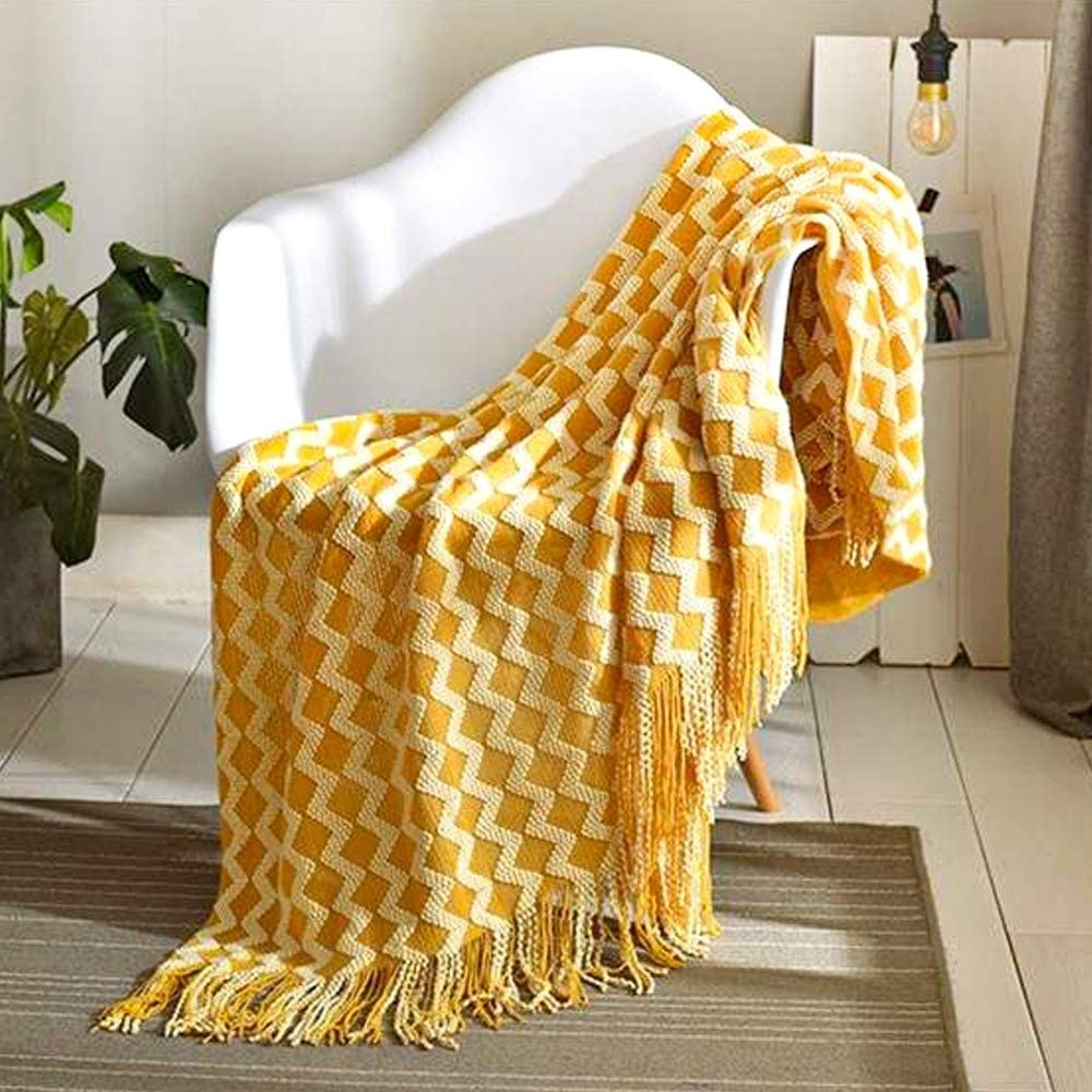 Yellow tasseled blanket with white, three dimensional zigzag pattern