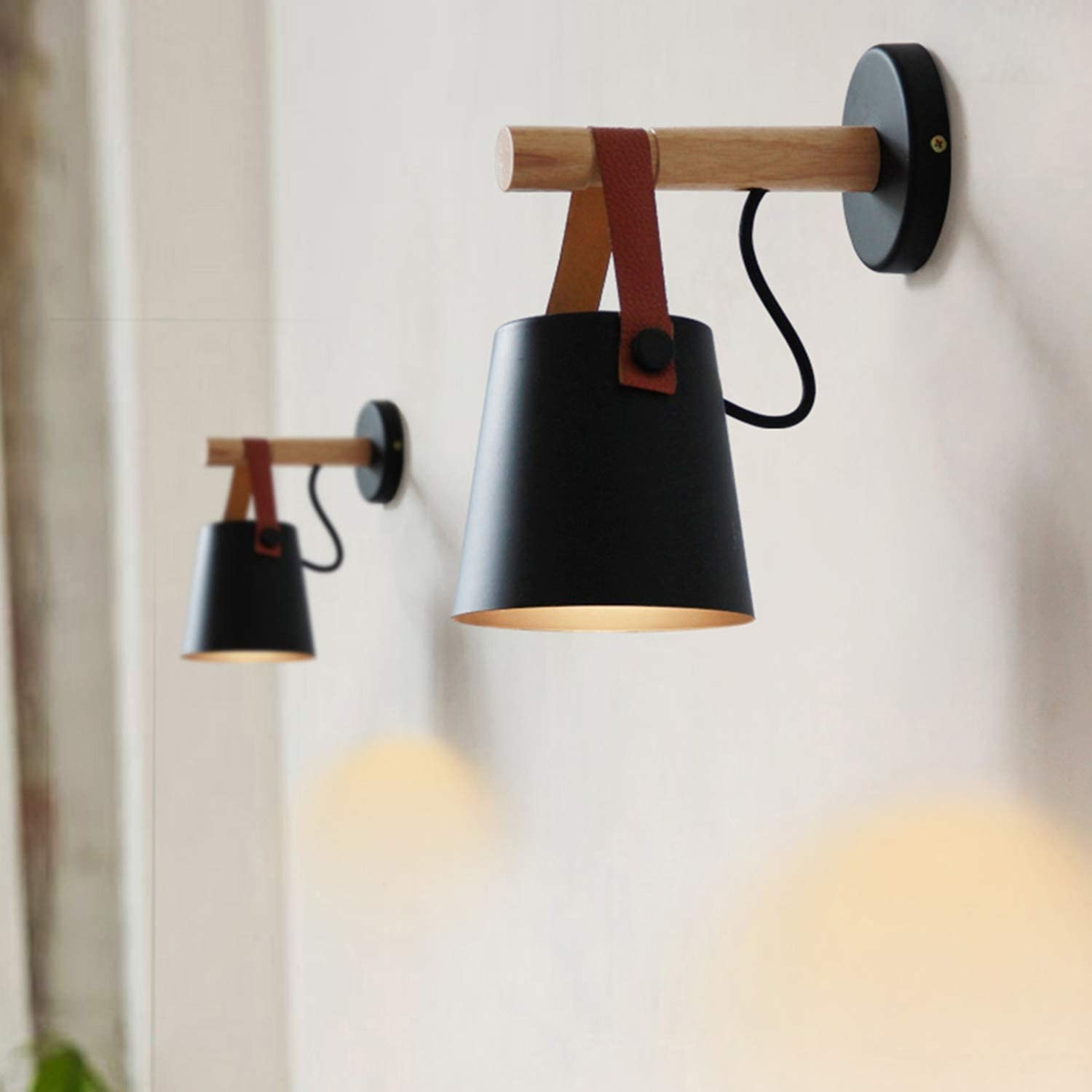 Black metal light shade with leather strap mounted to wooden peg on black metal base