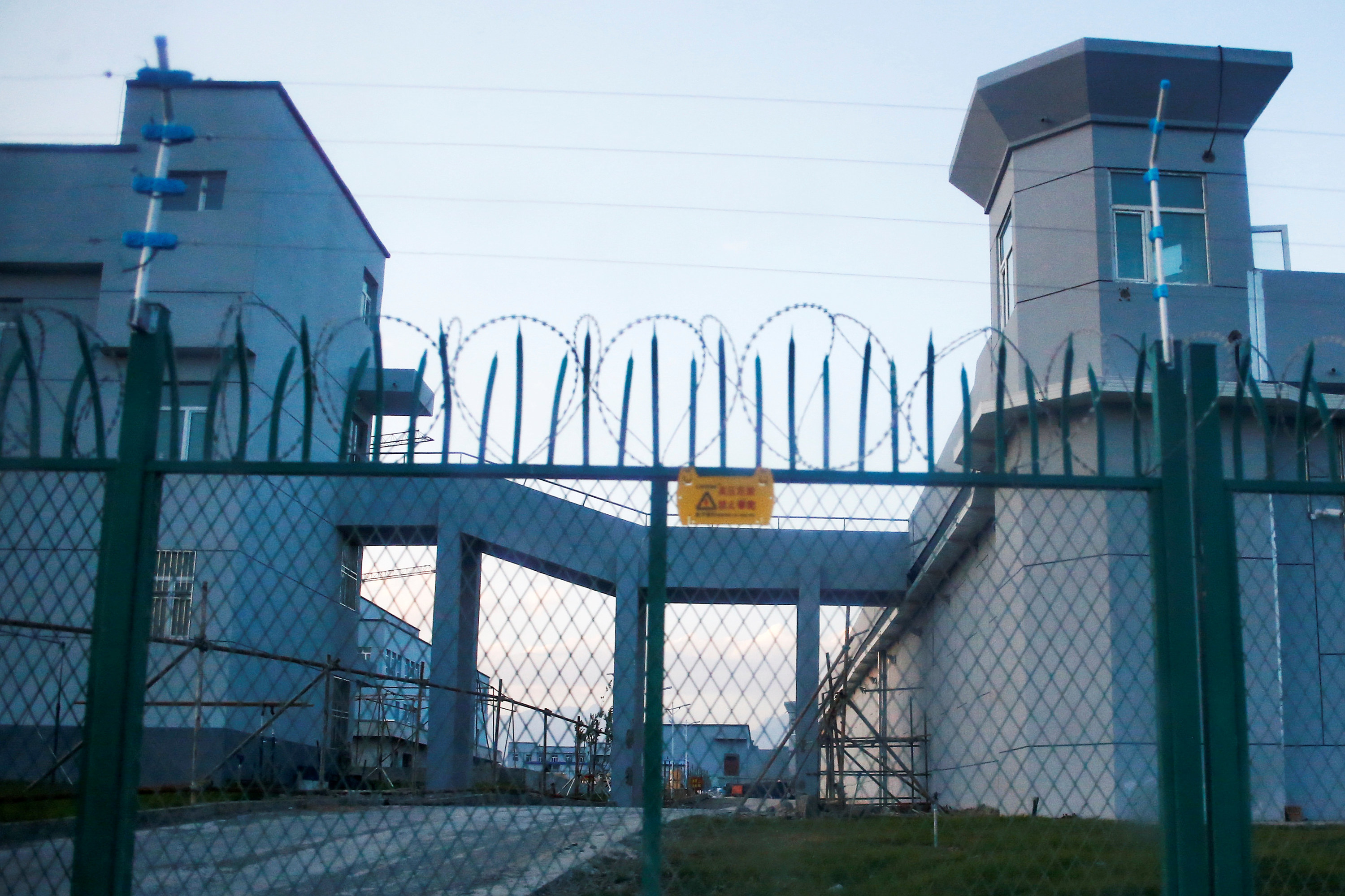 Barbed wire lines the top of a spiked fence in front of a large prisonlike complex