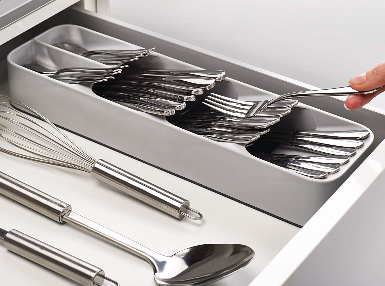 Model's fingers removing a fork from a neat stack of utensils in a gray plastic utensil organizer with five sections for knives, spoons, and more