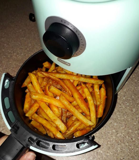 A reviewer pulling out the basket from the light blue air fryer containing perfectly cooked french fries