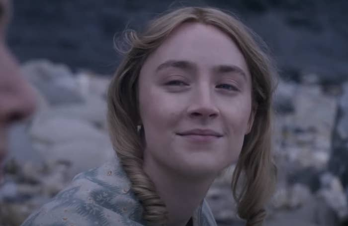 Saoirse Ronan looking wistfully at Kate Winslet on the beach